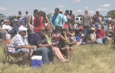 A crowd of people sitting on chairs in the grass